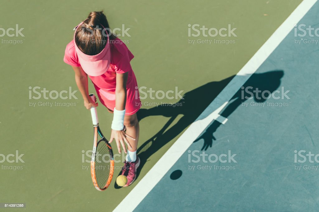 Young girl playing tennis, preparing to serve stock photo