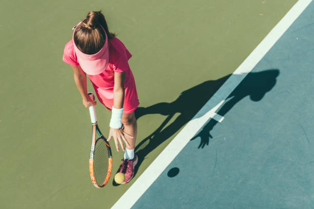 young girl playing tennis, preparing to serve - tennis stock pictures, royalty-free photos & images