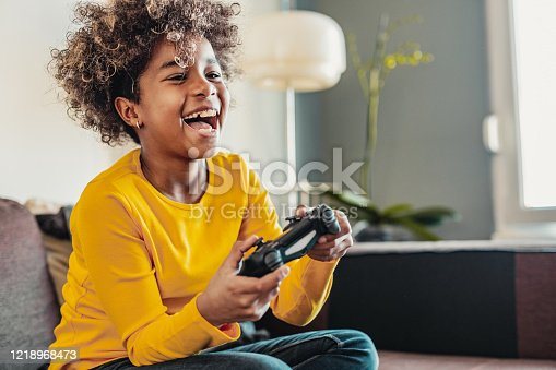 Young African American little girl at home with playing video games