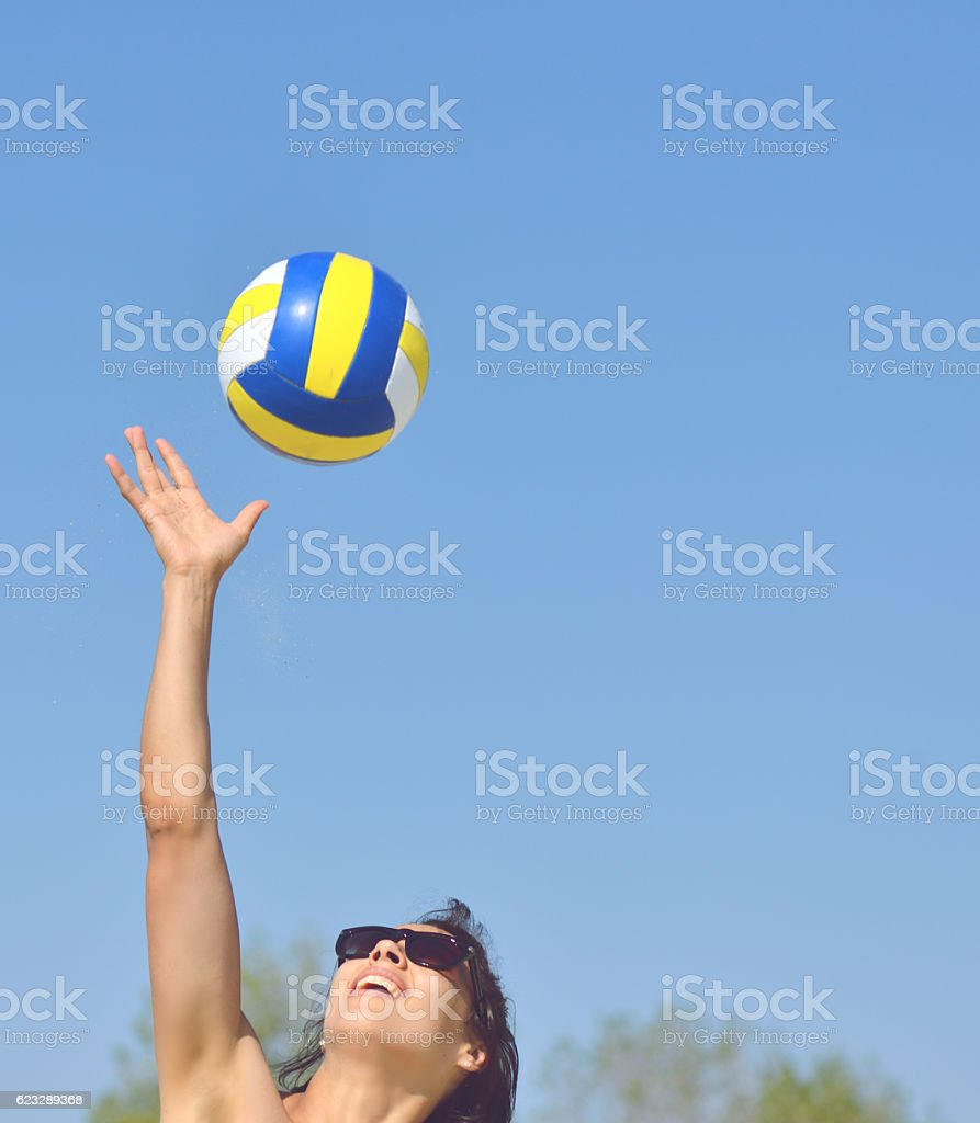 Young girl playing volleyball in the beach stock photo
