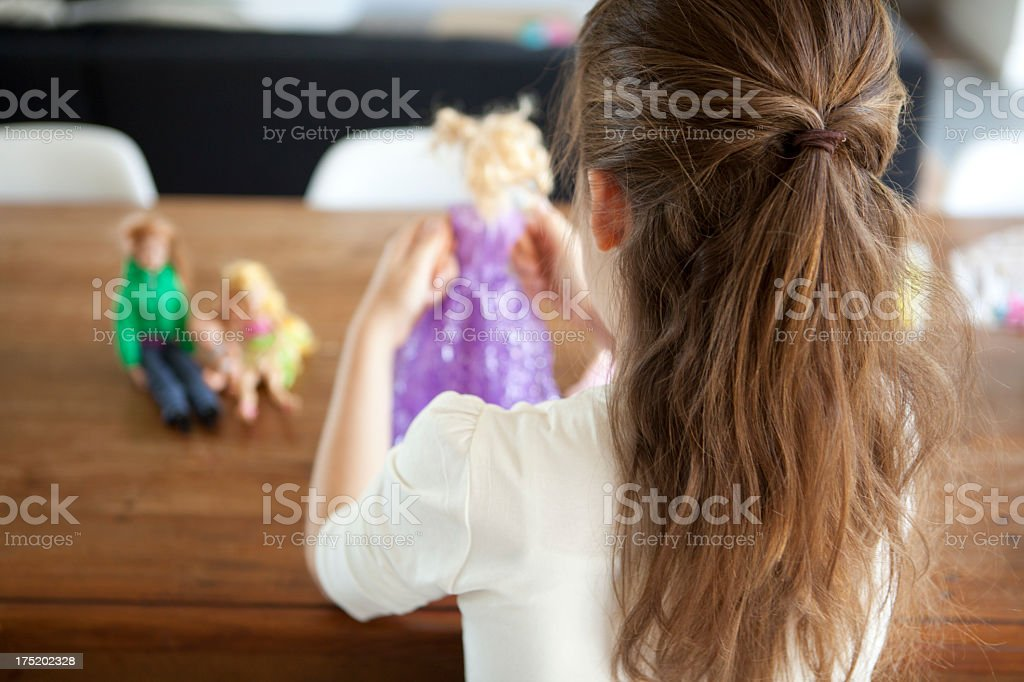 A young girl playing with dressed up dolls stock photo