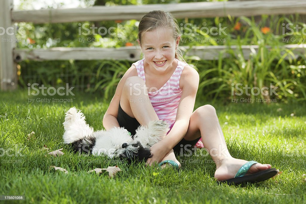 Young Girl Playing with Family Pet Dog in Grass Lawn royalty-free stock photo