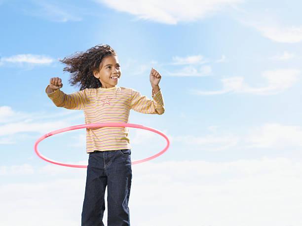 junges mädchen spielen mit hula-hoop - hula hoop workout stock-fotos und bilder