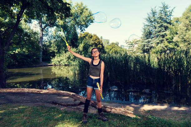 junges mädchen mit seifenballons in einem stadtpark sommerzeit selective focus - frisuren mit kurzen zöpfen stock-fotos und bilder