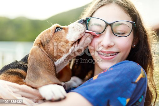 A DSLR Canon photo of a young girl playing with the dog while giving him a bath.