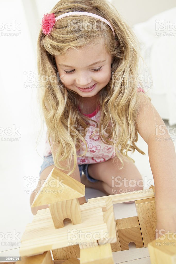 Young Girl Playing With Wooden Building Blocks royalty-free stock photo