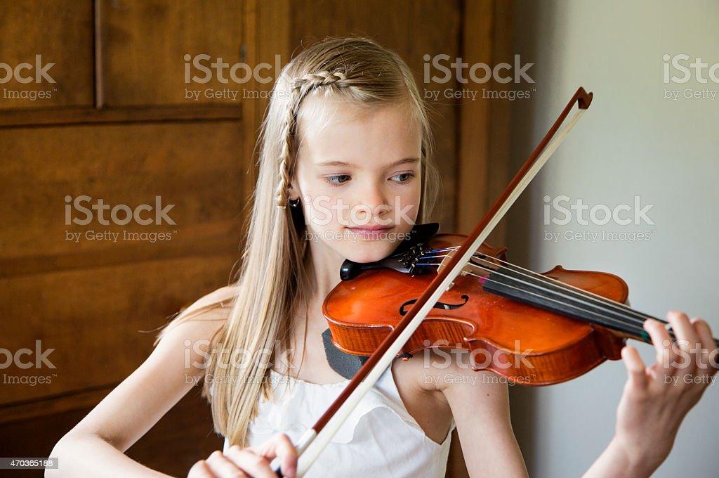 Young girl plays violin stock photo