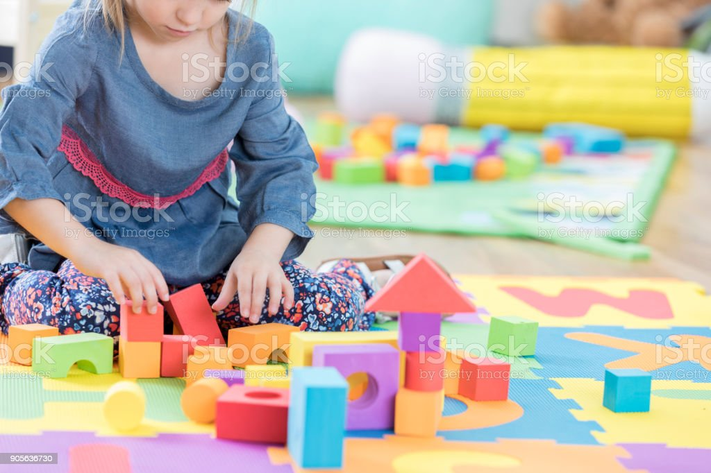 Interested little girl builds something with building blocks during...