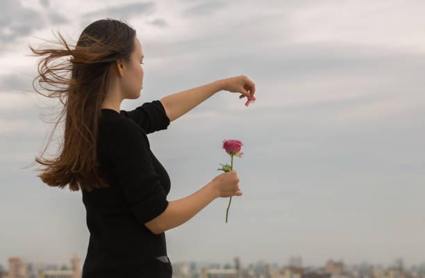 若い女の子はシティー ビュー上バラの花びらを駆り立てる - ロマンス ストックフォトと画像