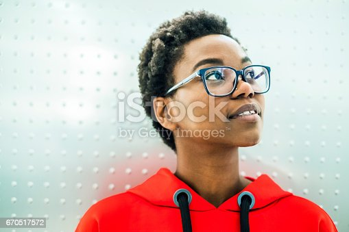 Young european african descent girl, in a red sweatshirt, looking up in front of a silver background. She wears glasses.