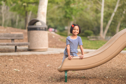 A young girl poses by the slide at the playground
