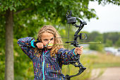 Close-up of a young girl (nine years old) practicing shooting her bow and arrow at an outdoor archery range on a fall day. The girl has her arrow drawn and is aiming at a target - not visible in this image.