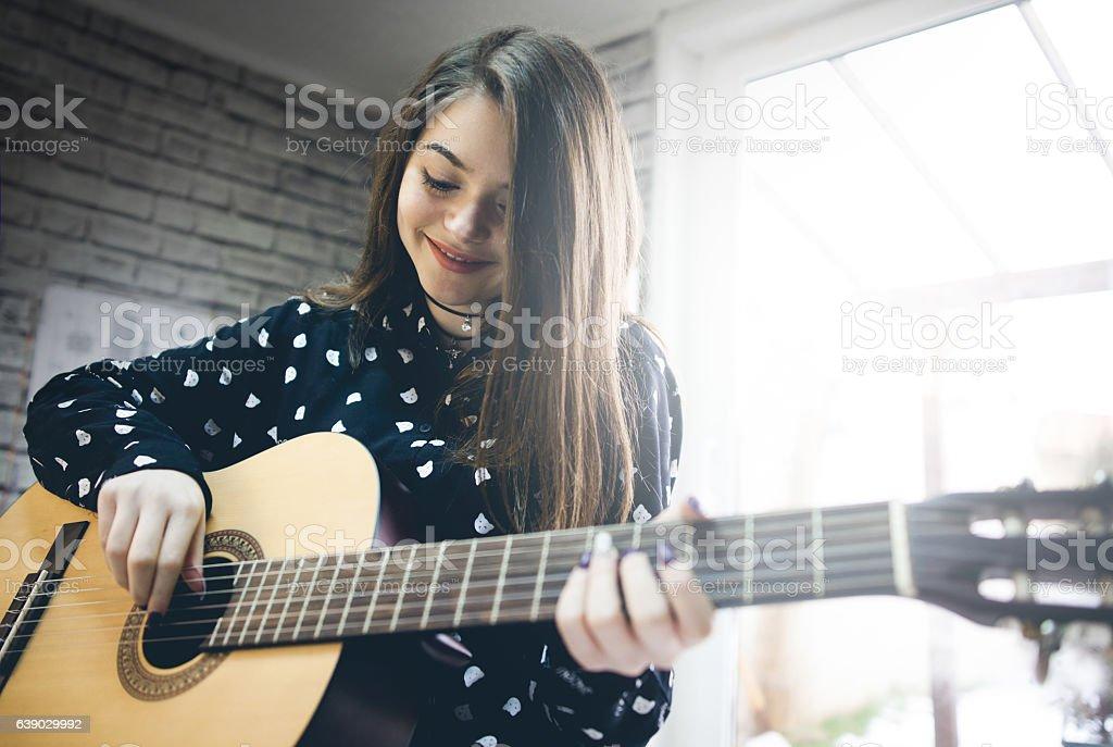 Young girl  practicing guitar. stock photo