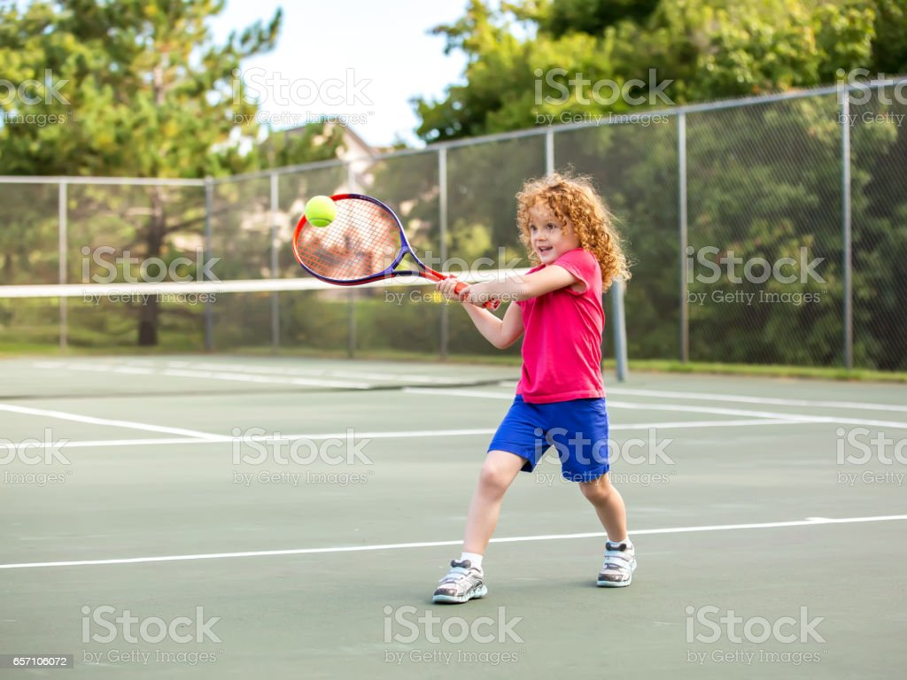 Young Girl Practicing Playing Tennis stock photo