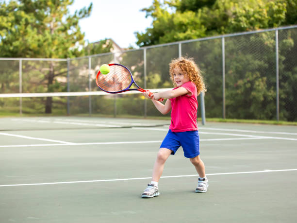 young girl practicing playing tennis - tennis stock photos and pictures