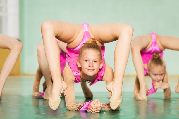 young girl practicing rhythmic gymnastics in gym - leotard stock photos and pictures