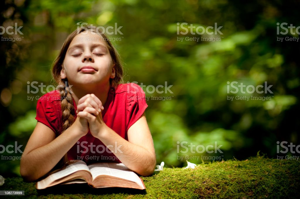 Young girl praying on a tree outdoors stock photo
