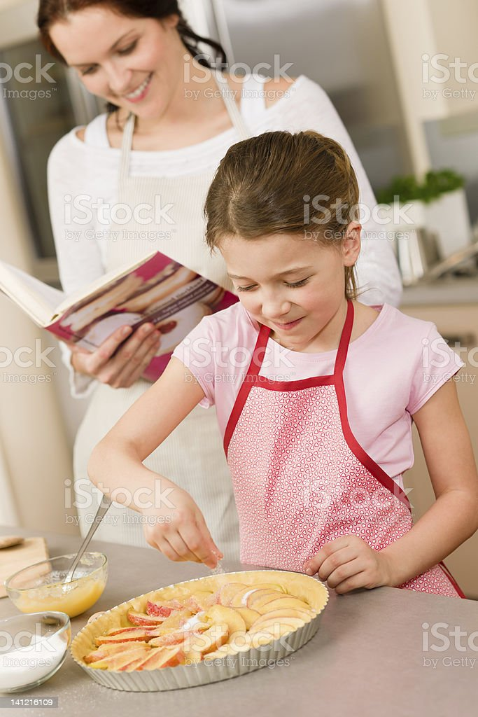 Young girl prepare apple pie with mother royalty-free stock photo