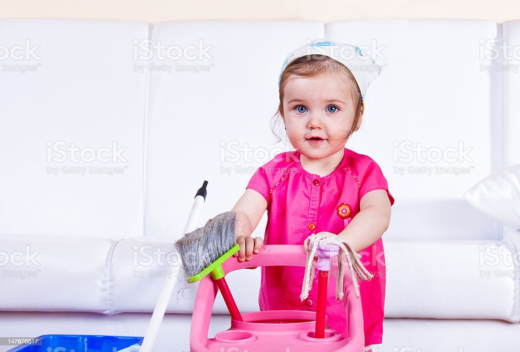 Young girl pretending to do housework with cleaning toys royalty-free stock photo