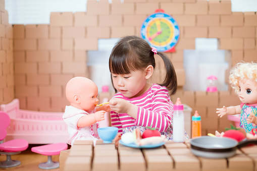 young girl pretends play babysitting with baby doll at home