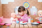 istock young girl pretends play babysitting with baby doll at home 1270127834