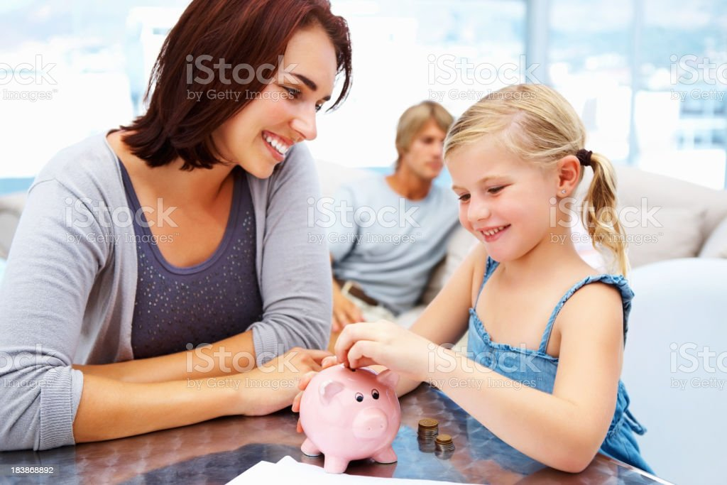 Young girl putting coins in piggy bank with mother watching royalty-free stock photo