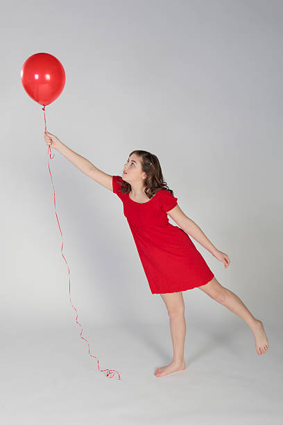 Young Girl Reaching for a Red Balloon stock photo
