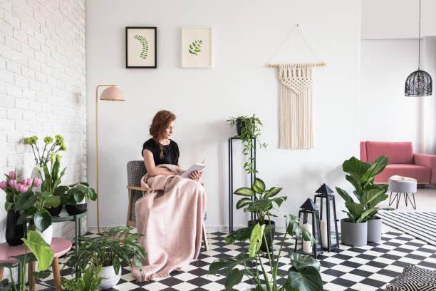 junges mädchen, ein buch lesen, bedeckt mit decke im wohnzimmer interieur mit pflanzen und karierten boden - deckenleuchte kinderzimmer stock-fotos und bilder