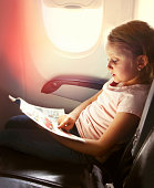 Young girl reading a magazine during flight