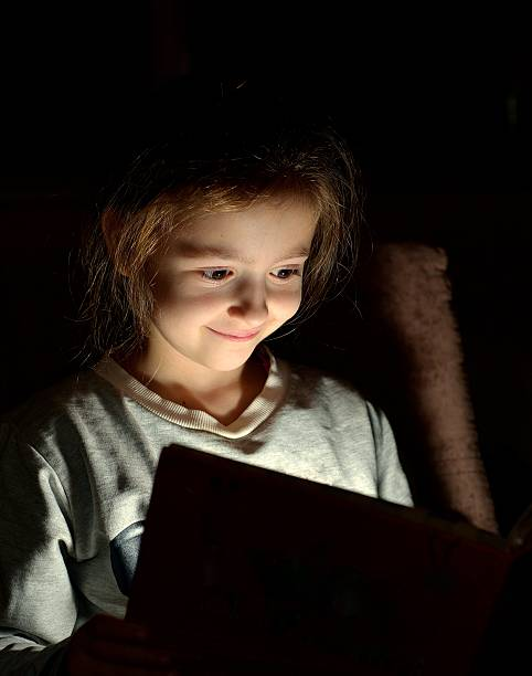 Cтоковое фото Young girl reading book at night