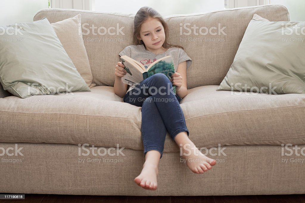 young girl reading book on sofa stock photo