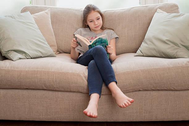 giovane ragazza lettura libro sul divano - bambine femmine foto e immagini stock