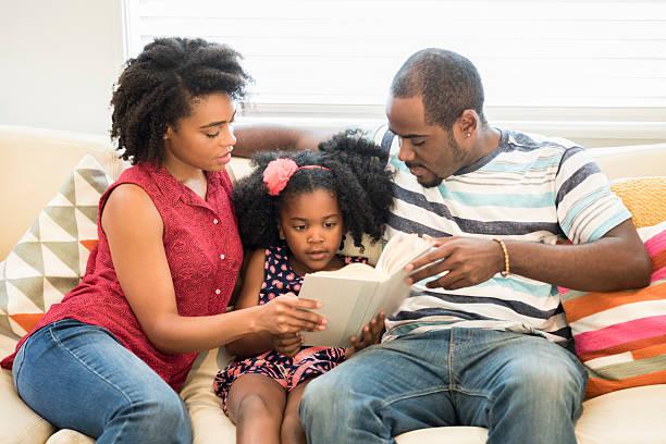 young girl reading book sitting between her parents - haushaltsbuch führen stock-fotos und bilder