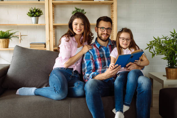 Young girl reading book while sitting on sofa with her parents stock photo