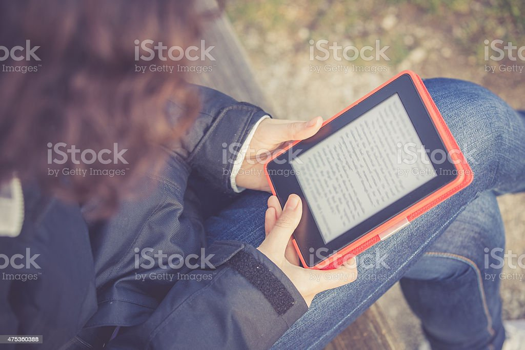 Young Girl Reading E-book at Park stock photo
