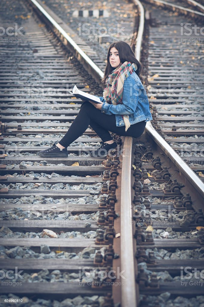 Young girl reading on the railway stock photo