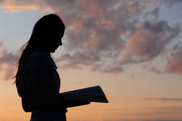Young girl reading Silhouette of a young girl reading from bible in sunset light.Please feel invited to view my photos from lightboxex! judaism stock pictures, royalty-free photos & images