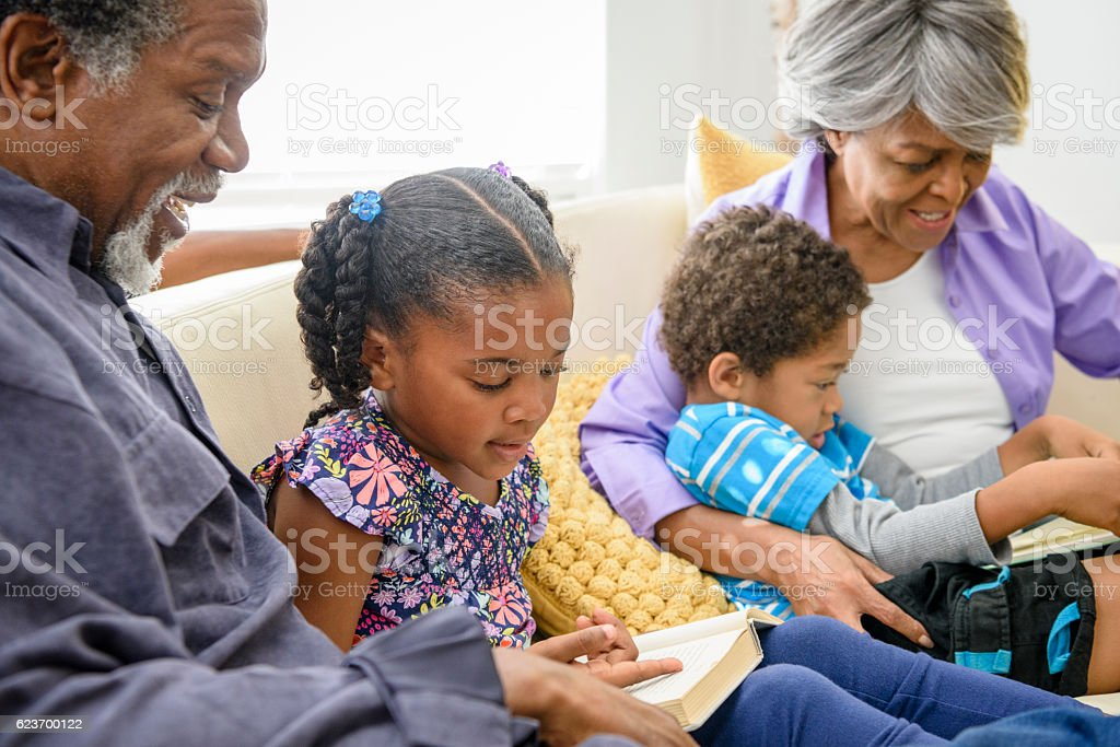 Young girl reading to African American grandfather on sofa stock photo