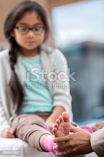 istock Young girl receives treatment for injured ankle 638551662
