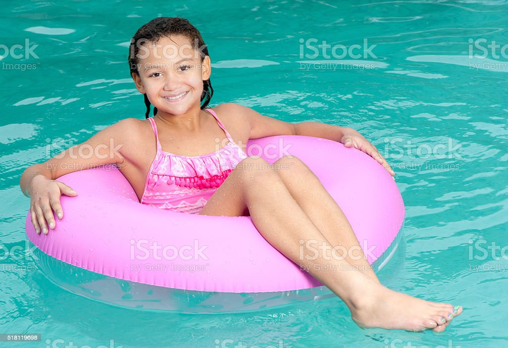 Young girl relaxes in swimming pool. stock photo