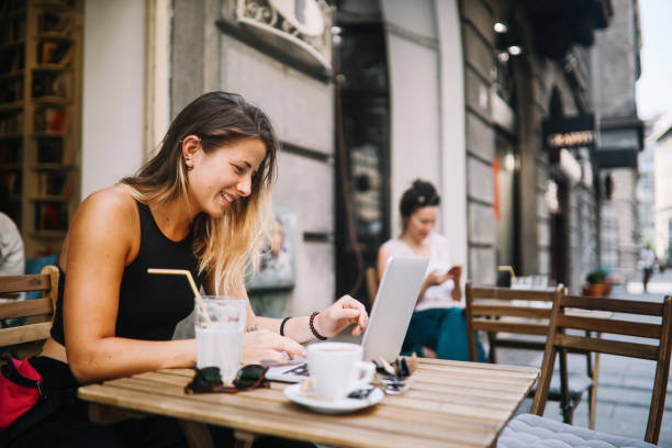 Young girl relaxing in a cafe, doing some online shopping stock photo