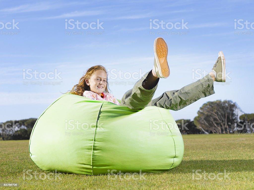 Młoda dziewczyna relaks w Worek do siedzenia na zewnątrz zbiór zdjęć royalty-free