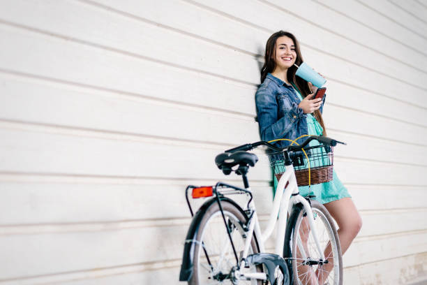 Young girl rents a bicycle from her smartphone. City bike