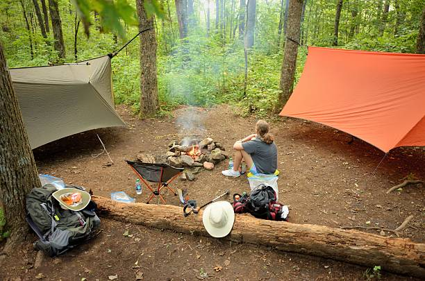 young girl resting by campfire in wooded campsite - planenzelt stock-fotos und bilder
