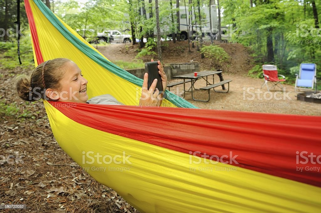 Young girl resting in hammock with rv and electronic tablet royalty-free stock photo