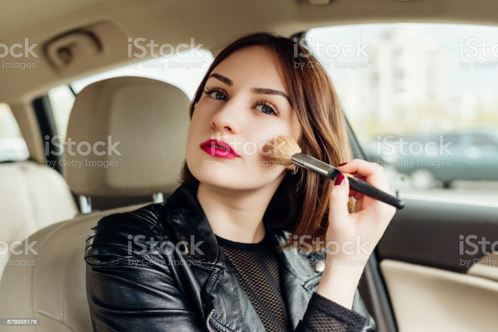 Young girl retouching her makeup while stopped in the traffic royalty-free stock photo