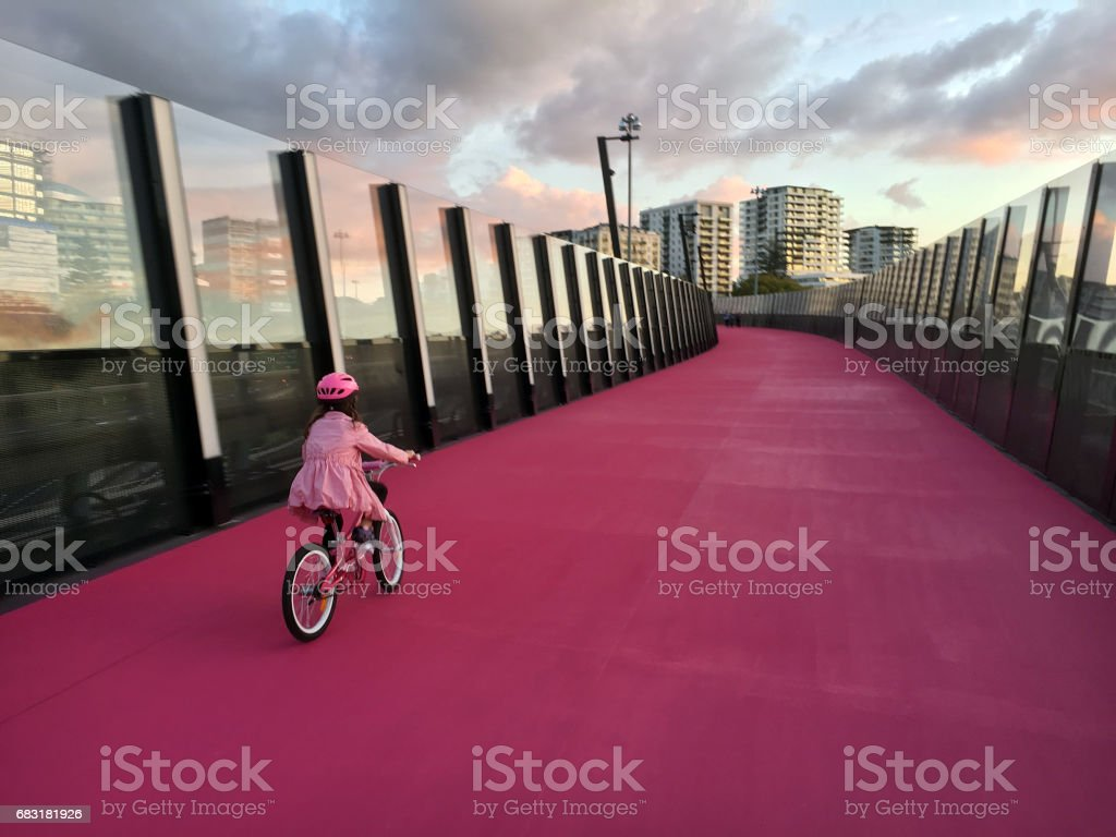 Young girl ride a bike on  bright pink cycleway in Auckland New Zealand stock photo