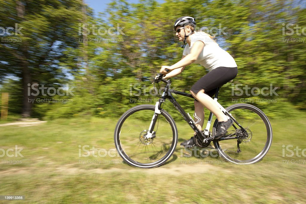 Young girl riding a bike on  field path - offroad royalty-free stock photo
