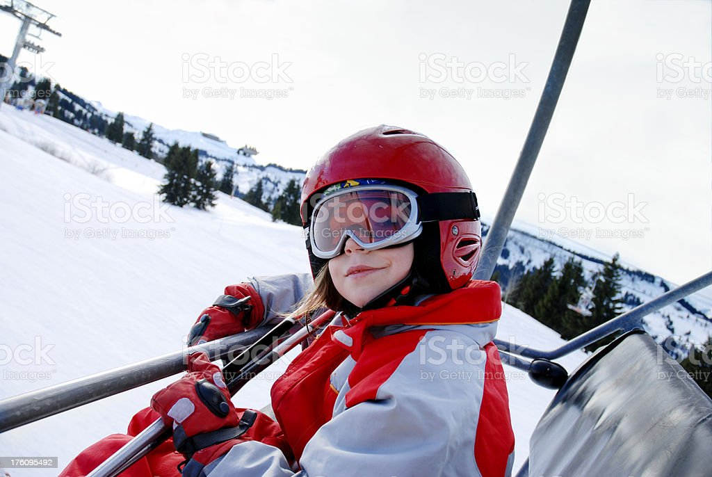 Young girl riding a chairlift. royalty-free stock photo