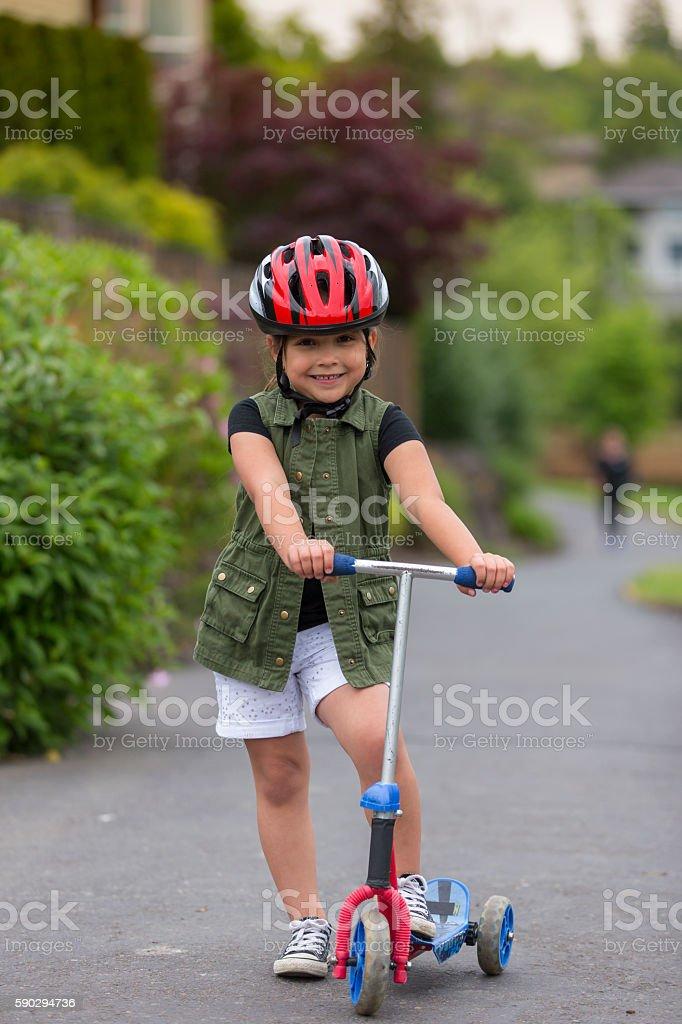 Young girl riding a scooter royaltyfri bildbanksbilder